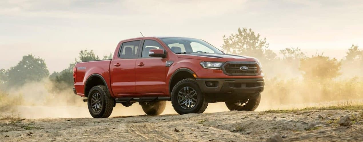 A red 2021 Ford Ranger Tremor Lariat is shown from the side parked on a dirt path.