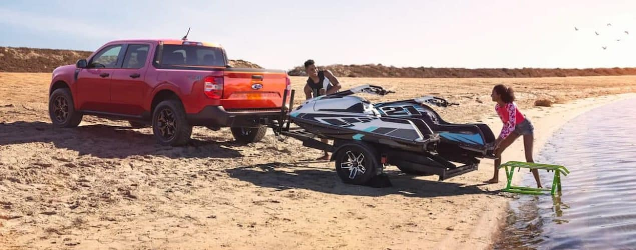 A red 2022 Ford Maverick is shown from the side next to a lake with a jet ski on the trailer.