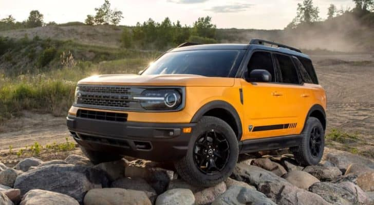 A yellow 2021 Ford Bronco Sport First Edition 4-door is shown from the side parked on a pile of stones.