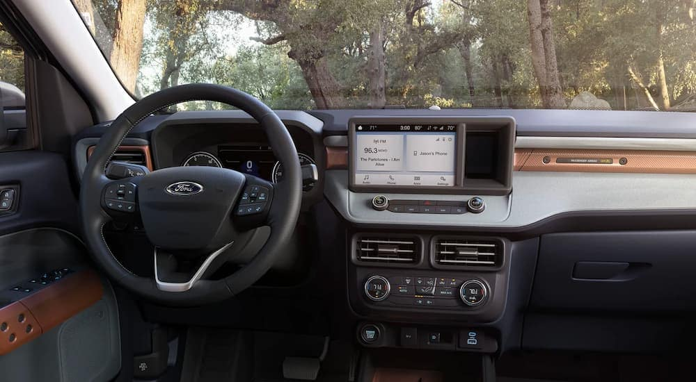 The black interior, steering wheel, and infotainment screen is shown in a 2022 Ford Maverick.